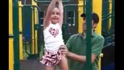 LIttle Girl Plays on the Monkey Bars, Needs Help From Dad